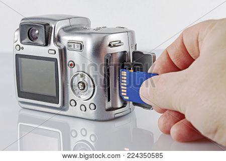 Old camera with a flash card. The hand inserts the flash drive into the camera.