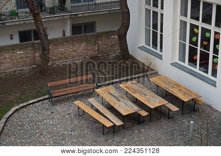 Wooden tables and benches stand in the courtyard. Wien, Austria