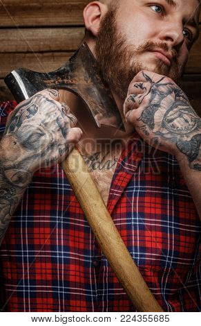 Brutal huge male with tattooes shaves his beard with a big axe