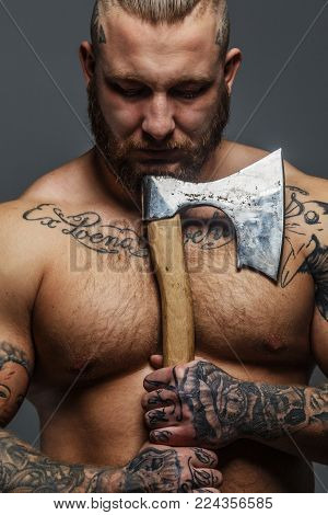 Huge brutal male with beard and tatooes holding axe