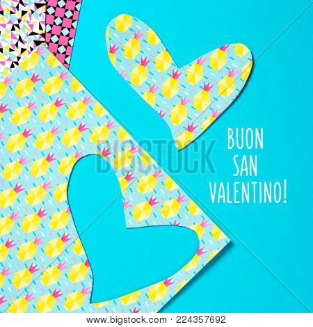 a heart cut out from a colorful abstract-patterned paper and the text buon san valentino, happy valentines day in Italian, against a bright blue background