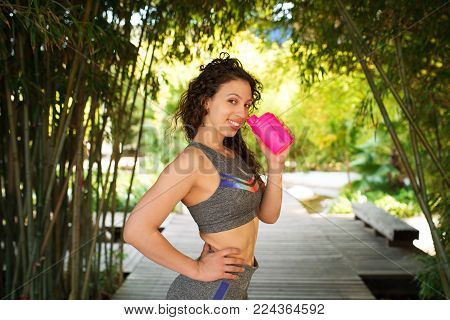 Smiling sporty Caucasian girl with sport supplement in pink shaker in garden. Young lady recovering after morning training in city park. Sport and fitness concept