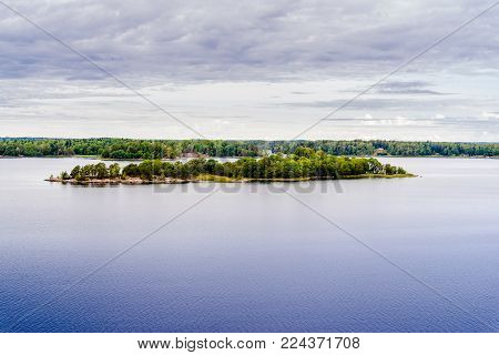 Beautiful panoramic view of Stockholm archipelago, Sweden. Green nature, little rock islands and deep water. Summer day with clouds.