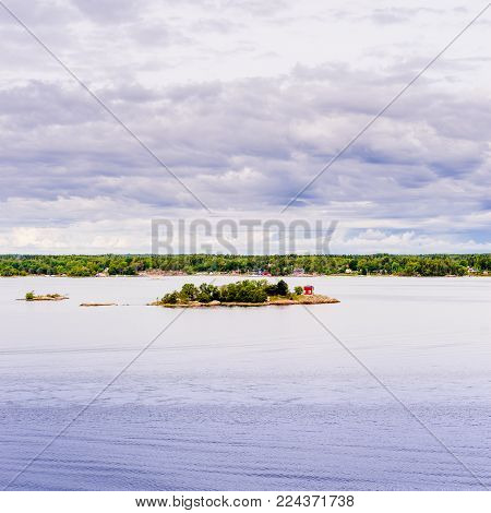Beautiful super wide-angle panoramic view of Stockholm archipelago, Sweden. Red little houses and green nature. Skyline with scenery beyond the city. summer day with blue clouds and deep water