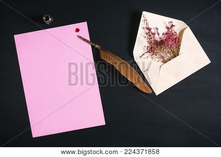Quill pen on a blank paper sheet and flowers - Open envelope full with red flowers, an antique feather pen on a pink paper note with a red ink splash on a black wooden background.