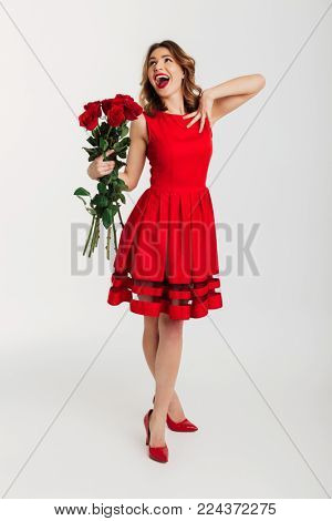 Full length portrait of a flattered young woman dressed in red dress holding bouquet of roses while standing and looking at camera isolated over white background