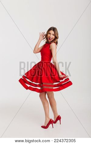 Full length portrait of a smiling petty girl dressed in red dress posing while standing and waving hand isolated over white background