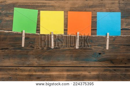 colorful blank note cards hanging from clothesline over a wooden background