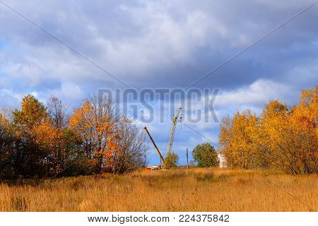 A construction crane in the autumn period on a blue sky. In the foreground a meadow, in the background construction crane, forest and blue sky.