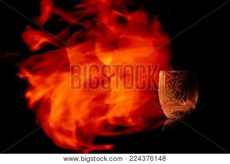 Faceted shot vodka, tequila and Sambuca isolated on black background in the fire flames.