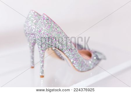 Beautiful silver glitter high heel female shoes on   glass shelf. Wedding accessories. Cinderella shoes. Selective focus.