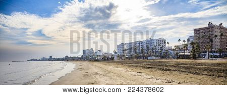 Finikoudes sandy beach at Larnaca, Cyprus. Blue sky and white clouds for backdrop. Space, banner