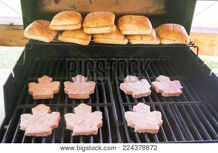 Picture of hamburger buns and maple leaf shaped hamburgers on a grill.