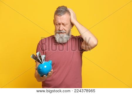 Troubled senior man with dollar banknotes and piggy bank on color background