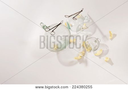 Transparent round glass balls cast long shadows on a white background, on the surface of the balls lie long surgical scissors, yellow rose petals strewn with petals, modern design interior of wall.