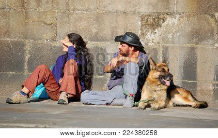 A pilgrim couple and their dog enjoys a brief rest on a sunny spot - Santiago de Compostela, Galicia, Spain, 25 September 2007