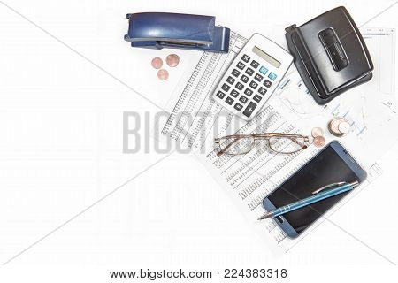 business calculation with number tables, calculator, glasses, smartphone and office supplies on a white desk, corner background, top view from above mock up, copy space