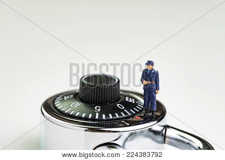 Computer security impact on IT business awareness concept, with miniature figure security guard standing on circle combination lock pad with turning code.