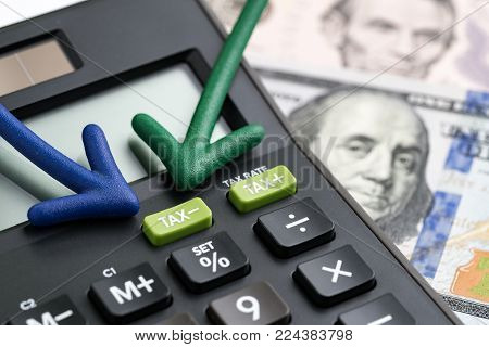United States tax cuts, reform / reduce concept, arrows pointing to TAX minus button on calculator with background of blurred US Dollar banknotes, government offer tax deduction policy.