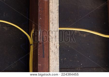 Close view of sistering of old and new wall studs against a construction felt backing with yellow electrical wiring, copy space, horizontal aspect