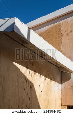 Detail of renovation or new construction building exterior with spray painted fascia board and plywood sheathing, copy space, vertical aspect poster