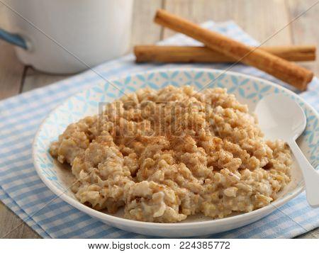 Oatmeal porridge with powdered cinnamon and cinnamon sticks