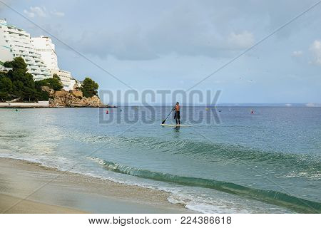 General view of the beach, a calm sea  and floating on a plank surfer on blue sky background