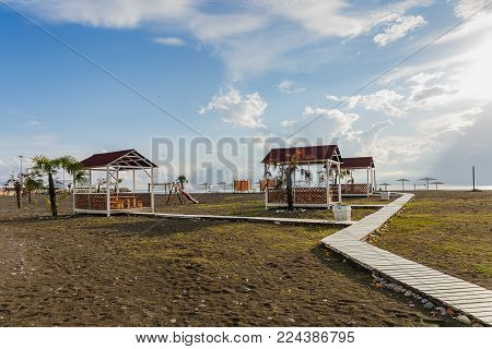 a view of the sandy beach with relaxing palapas and wooden walkways at sunset of a summer day
