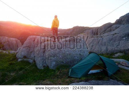Alone tourist near his tent in norvegian mountains. Located place - famous Preikestolen rock, Norway, Europe