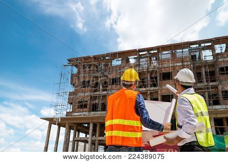Businessman engineer looking blueprint in a building to  discussion with architects at construction site or building site of highrise building