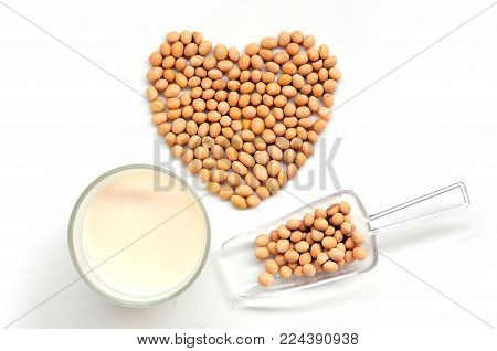 Top view of Glass soy milk and Soy bean in heart shape and scoop for valentine festival isolated on white background, food and drink healthy concept