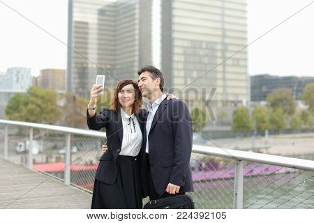 Marketer  and HR manager  taking selfie by smartphone, old friends suddenly meet during lunch break. Middle-aged American male and female wearing strict suits smiling. Concept of innovative technologies and gadgets, making photos with mobile