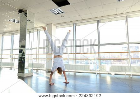 Male person making swipe and vigorous movements in white shirt and pants. Blonde dancer training at studio with large window and mirror. Concept of break dancing at gym.