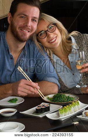Couple in love eat sushi rolls in Japanese restaurant.