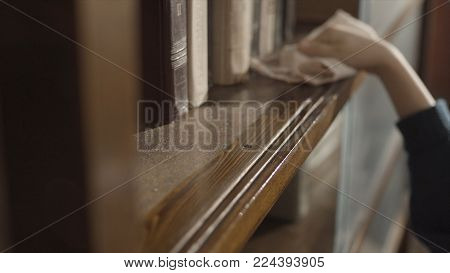 Close Up Of Kid's Hand Wiping A Dust On The Bookshelf. Child Clean Up The Shelf. Boy's Hand Clean Up