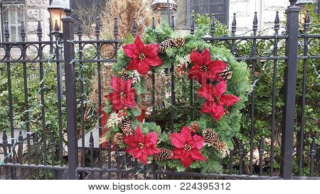 Green Christmas Holiday Wreath with red Poinsettia flowers adorning a black metal fence in winter