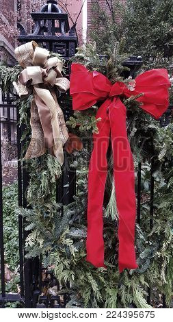 red and gold bows adorn a green Christmas holiday wreath on a black metal fence in winter