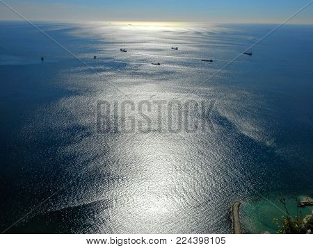 Aerial View Of Backside Of Rock Of Gibraltar With Shipping Harbor With Shipping Boats And Sunset In
