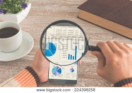 Investment and modern lifestyle concept. Women hands Use the magnifying glass screen smart phone for investment on the desk. Retro style.