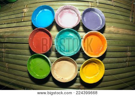 Multicolored Plastic Cups With Paints On Bamboo Table Background, Art Tools For Artist Workplace Bac