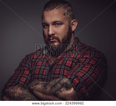 Portrait of serious bearded man with tattooed arms isolated on grey background.