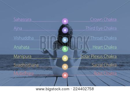 Woman meditating in lotus position outdoor. Chakra lights over her body. Yoga, zen, Buddhism, recovery and wellbeing concept.