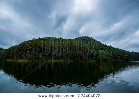 Forest Mountain behind the river with cloudy sky in the morning, Traveling in Thailand (Pang Ung)