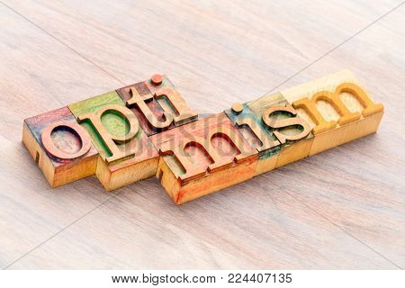 optimism word abstract in letterpress wood printing blocks stained by color inks