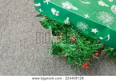 Pile Of Christmas Decoration In A Green Box On Gray Carpet Background
