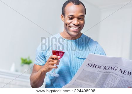 Morning newspaper. Joyful positive handsome man smiling and reading news while having a glass of wine
