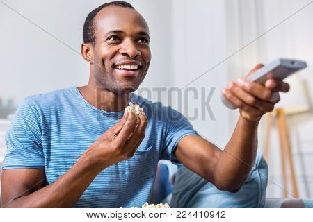Leisure time. Happy joyful adult man holding a remote control and eating popcorn while choosing a TV channel