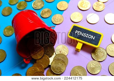 Top view of red pile with coins and blackboard written with 'PENSION' on blue and purple background. Two tone background.Business and finance theme.