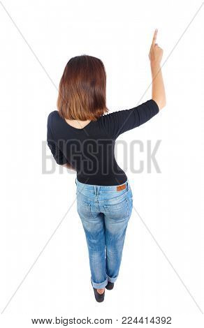 Back view of  pointing woman. beautiful girl. Rear view people collection.  backside view of person.  Isolated over white background. Top view of a girl in a black jacket showing her hand up.