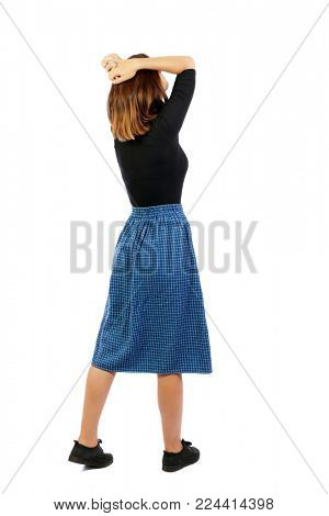 Back view of shocked woman in dress. upset young girl. Rear view people collection.  backside view of person.  Isolated over white background. A girl in a blue skirt in horror